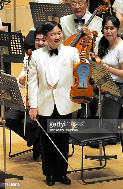 Crown Prince Naruhito shows the viola made of debris of the tsunami of the magnitude 90 earthquake in 2011 during the Gakushuin University Alumni...