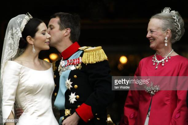 Crown Princess Mary and Crown Prince Frederik kiss as Queen Margrethe II of Denmark looks on as the Royal couple appear on the balcony of Christian...