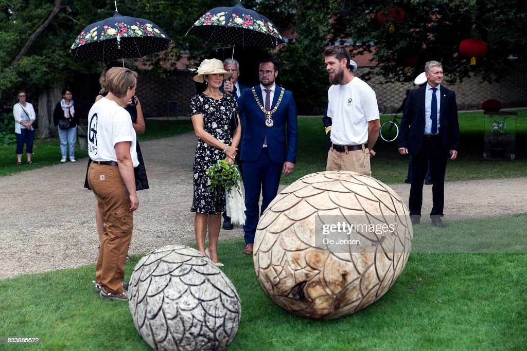 Crown Princess Mary (L - 2nd) is presented to garden art cut in wood by the company Guro during her visit to Odense Flower Festival which she is to open officially and where she is to be presented to a new developed rose on August 17, 2017 in Odense, Denmark. The festival opens today and ends August 20 and takes place all over the inner city with some 100.000 plants made up with the theme 'What a Woinderful World' and urban gardening.
