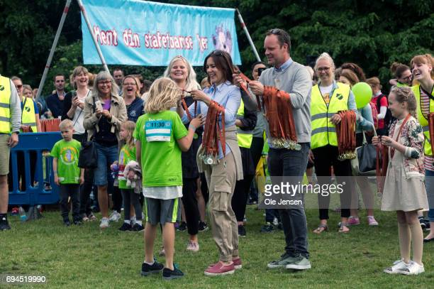 Crown Princess Mary of Denmark presents medal to the first runner passing the finishing line at the 'Children's Relay Run' in Faelledparken on June...