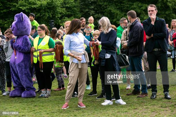 Crown Princess Mary of Denmark receives an arm's length of medals at the finishing line which she presents to the participants at the 'Children's...