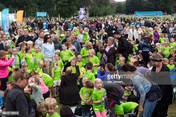 Crown Princess Mary of Denmark surrounded by kids during the warmup exercise at the 'Children's Relay Run' in Faelledparken on June 10 2017 in...