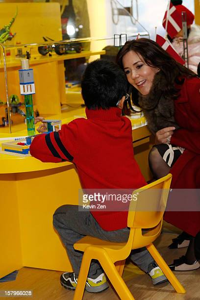 Crown Princess Mary of Denmark talks to a kid at the LEGO education centre in Chaoyang Park on December 8 2012 in Beijing China