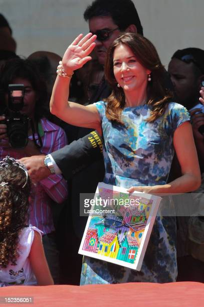 Crown Princess Mary of Denmark with receives a painting from a kid at Centro de Referência da Juventude during her visit to Cidade de Deus in Rio on...
