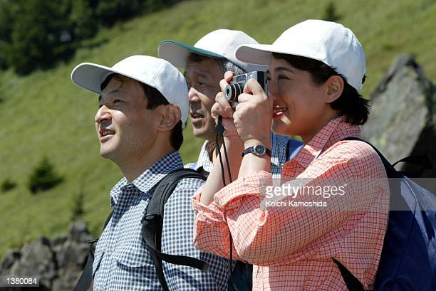Crown Princess Masako takes pictures of flowers and surrounding mountains as Crown Prince Naruhito stands next to her while on a mountain peak named...