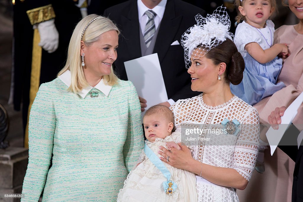 Crown Princess Mette-Marit of Norway, and Crown Princess Victoria of Sweden holding Prince Oscar, Duke of Skane after the ceremony at the Royal Palace in Stockholm for the Christening of Prince Oscar of Sweden on May 27, 2016 in Stockholm, Sweden.