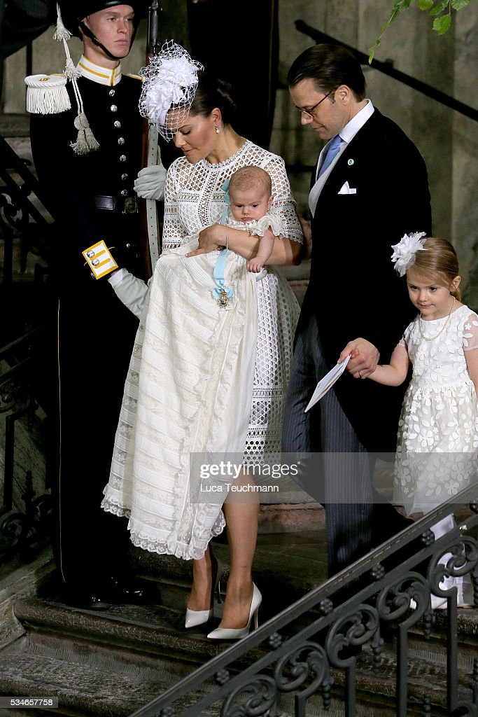Crown Princess Victoria of Sweden holds Prince Oscar, Duke of Skane and Prince Daniel, Duke of Vastergotland and <a gi-track='captionPersonalityLinkClicked' href=/galleries/search?phrase=Princess+Estelle&family=editorial&specificpeople=8948207 ng-click='$event.stopPropagation()'>Princess Estelle</a> of Sweden are seen at The Royal Palace for the Christening of Prince Oscar of Sweden on May 27, 2016 in Stockholm, Sweden.