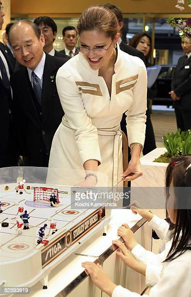 Crown Princess Victoria of Sweden plays a hockey game with Sweden's Minister for Industry and Trade Thomas Ostros at Matsuzakaya department store on...