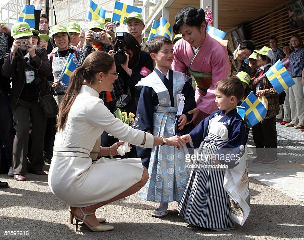 Crown Princess Victoria of Sweden receives a bouquet by Kevin Ahrlind who is living in local city Okazaki with his family at the Nordic Pavilion of...