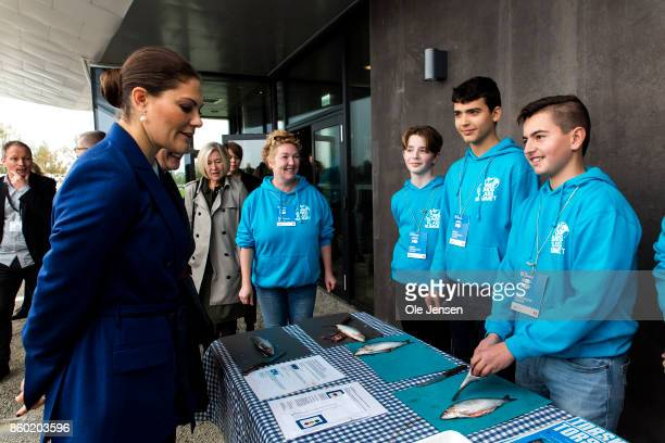 Crown Princess Victoria of Sweden speaks to young students about preparing herring for cooking at the new Marine Pedagogical Learning Center after...