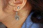 Crown shape of metal earring with diamond earring on the ear of long hair woman.
