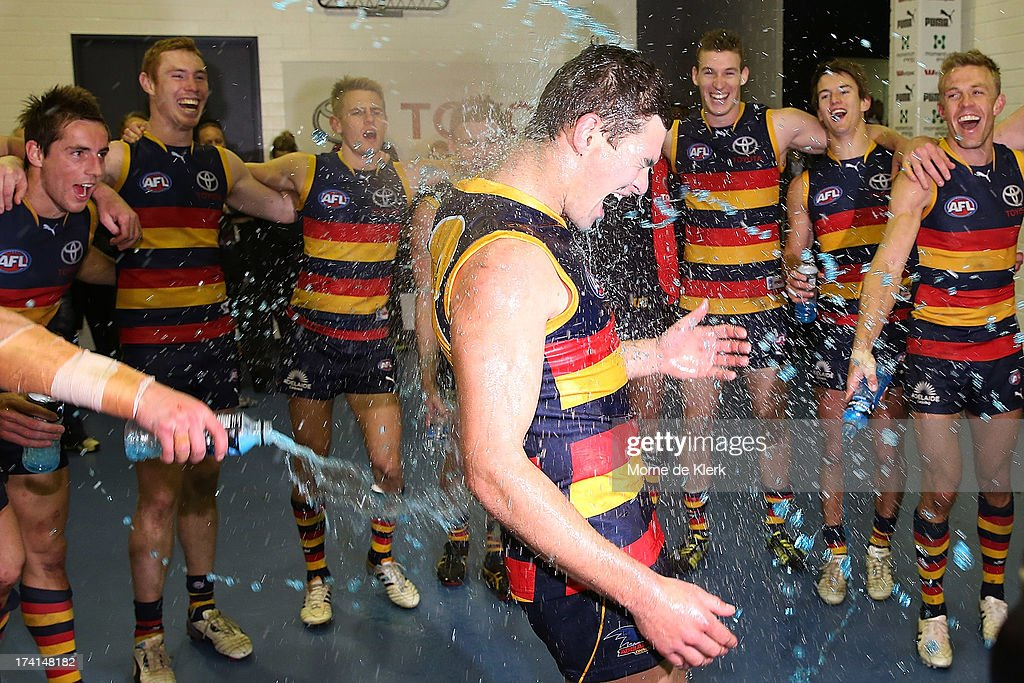 Crows players celebrate with Mitch Grigg after the round 17 AFL match between the Adelaide Crows and the Geelong Cats at AAMI Stadium on July 21, 2013 in Adelaide, Australia.