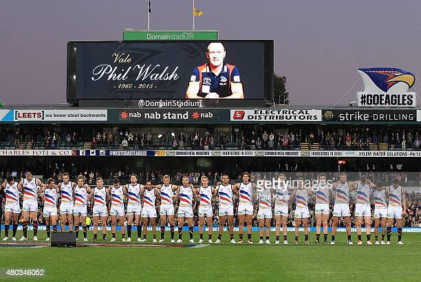 Crows players line up for a moments silence to pay respect to their coach Phil Walsh during the round 15 AFL match between the West Coast Eagles and...