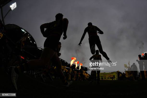 Crows players run onto the field prior to the round 20 AFL match between the Adelaide Crows and the Port Adelaide Power at Adelaide Oval on August 6...