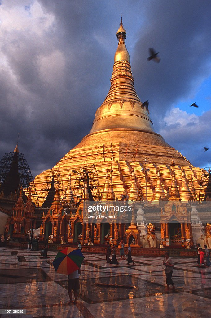 Crows swarm and the faithful circle around the Shwedagon Paya following a downpour. The temple is considered one of Burma's holiest Buddhist sites..