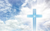 Crucifix cross on beautiful sky with sunbeam. Holy cross of Jesus christ on clouds background.
