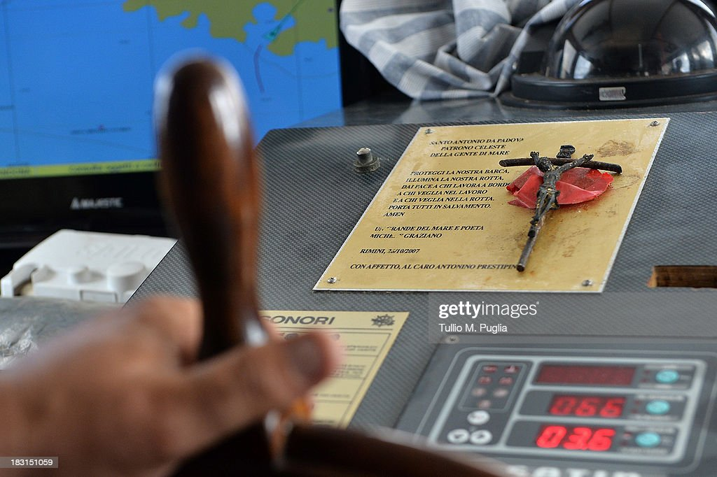 A Crucifix is seen on the dashboard of a fishing vessels sailing off the Lampedusa shore after laying a wreath in memory of victims of a immigrants disaster over the Lampedusa shore on October 5, 2013 in Lampedusa, Italy. The search for bodies continues off the coast of Southern Italy as the death toll of African migrants who drowned as they tried to reach the island of Lampedusa is expected to reach over 300 people. The tragedy has bought fresh questions over the thousands of asylum seekers that arrive into Europe by boat each year.