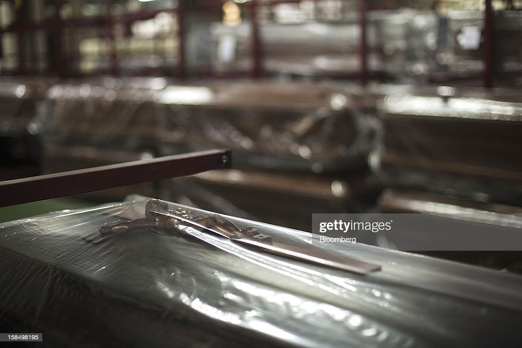 A crucifix is seen through protective plastic sheeting on a wood coffin in the storage warehouse of the Empresa Mixta de Servicios Funerarios de Madrid SA funeral parlour in Madrid, Spain, on Monday, Dec. 17, 2012. Spain, responding to street protests and reports of suicides linked to foreclosures, introduced rules to help protect families from eviction, increasing the risk of creditor losses and weakening an already fragile banking system. Photographer: Angel Navarrete/Bloomberg via Getty Images