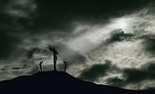 A depiction of the crucifixion of Jesus Christ on a cross with 2 other robbers nearby on Calvary. The sky is darkened with rays of light breaking through the clouds onto the cross for drama. Concept o