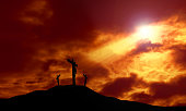 A depiction of the crucifixion of Jesus Christ on a cross with 2 other robbers against a dramatic sunset with rays of light breaking through the clouds onto the cross and lens flare for effect. Concep