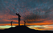 A silhouette of the crucifixion of Jesus Christ on a cross with 2 other robbers against a dramatic sunset. Concept of the death of Jesus on Good Friday and His resurrection on Easter Sunday. Horizonta