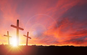A silhouette of the crucifixion of Jesus Christ on a cross with 2 other robbers against a dramatic sunset. Sacrificial death of Jesus on Good Friday and His resurrection on Easter Sunday with copy spa
