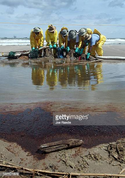 Crude oil lays on the ground in the foreground as workers are seen moving absorbent material as they try to capture some of the oil washing on to...
