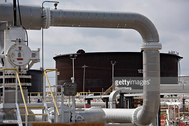 A crude oil storage tank stands beyond a manifold at the Enbridge Inc Cushing storage terminal in Cushing Oklahoma US on Wednesday March 25 2015 The...