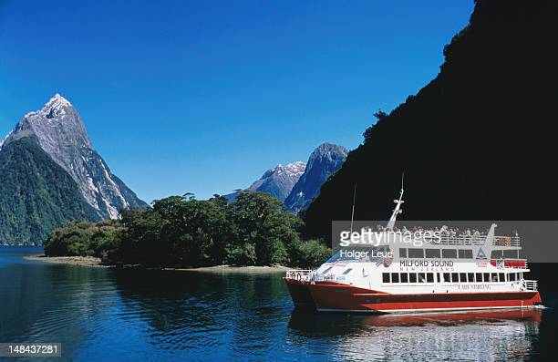 Cruise boat on Milford Sound with Mitre Peak in background at left.