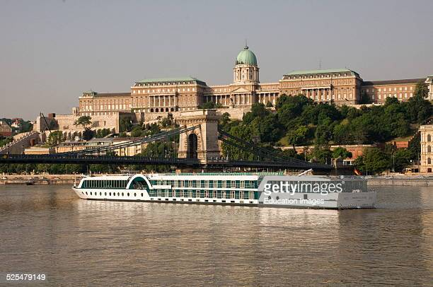 Cruise boat passing below the Royal Palace on the Danube River Budapest Hungary