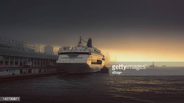 Cruise liner docking in Victoria Harbour at sunset