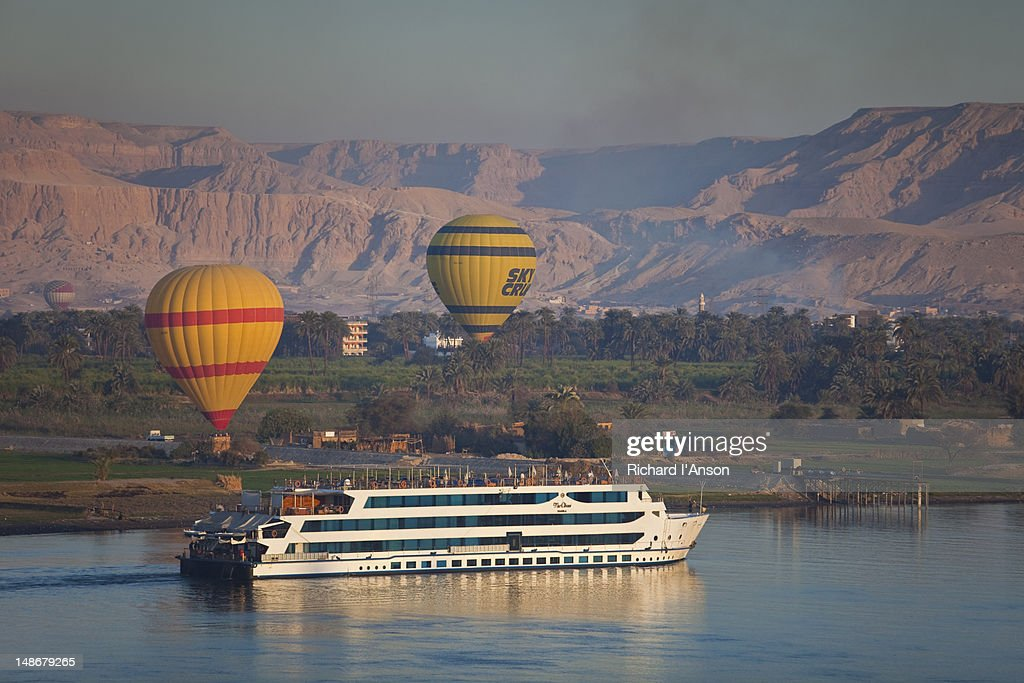 Cruise ship on Nile River & hot air balloons at sunrise.