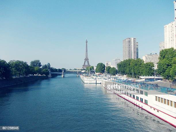 Cruise Ship On Seine River By Buildings In City Against Clear Sky