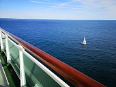 An ocean liner passes a yacht on a vibrant blue sea - over looking a safety hand rail.