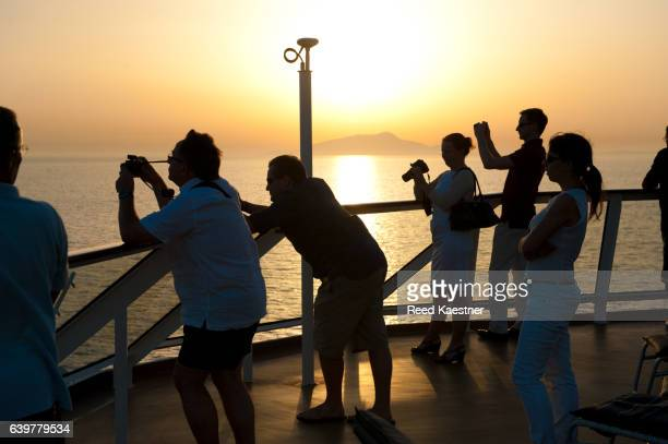 Cruise ship passengers take photographs at sunset over looking Capri, Italy