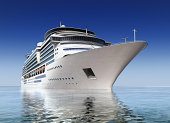 luxury white cruise ship shot at angle at water level on a clear day.