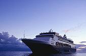 Cruise ship sailing on open sea at sunset