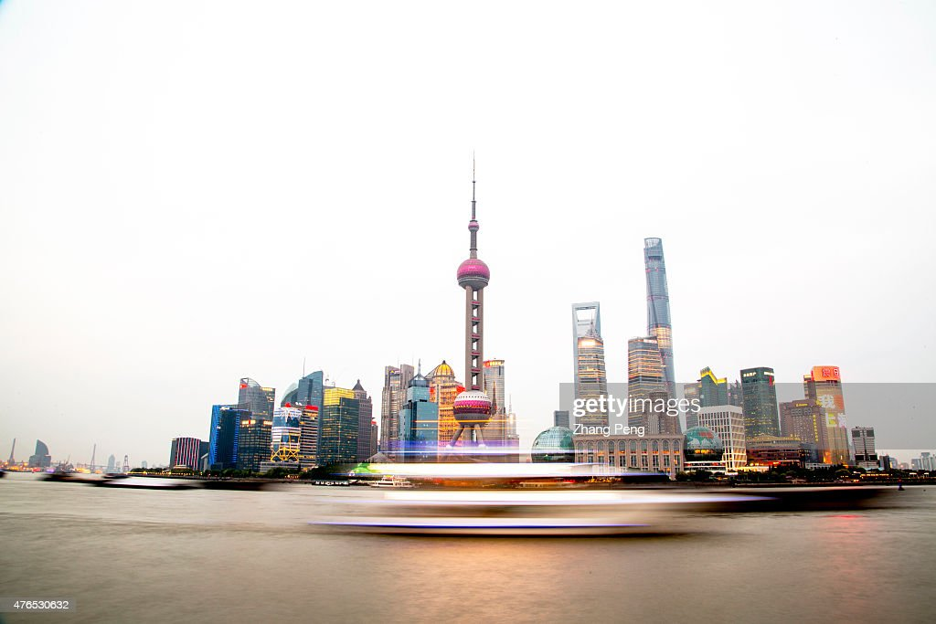 Cruise ship sails on the Huangpu river under the Oriental pearl tower which is the landmark of Shanghai Pudong