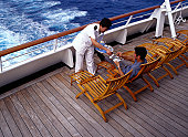 Cruise Ship Waiter Serving Coffee to a Passenger