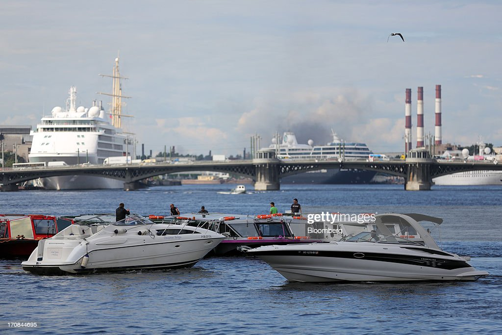 Cruise ships operate on the Neva river beyond motorboats and the Blagoveschensky bridge ahead of the St. Petersburg International Economic Forum 2013 (SPIEF) in St. Petersburg, Russia, on Wednesday, June 19, 2013. The Russian Deputy Prime Minister Igor Shuvalov told the conference that the country's World Trade Organization accession negotiations could be further delayed unless several remaining disputed matters are solved. Photographer: Andrey Rudakov/Bloomberg via Getty Images
