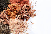 crumbled eyeshadows of different colors on a white background horizontal, space for text