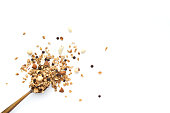 Crumbled granola with a wooden spoon on a white background. Top view