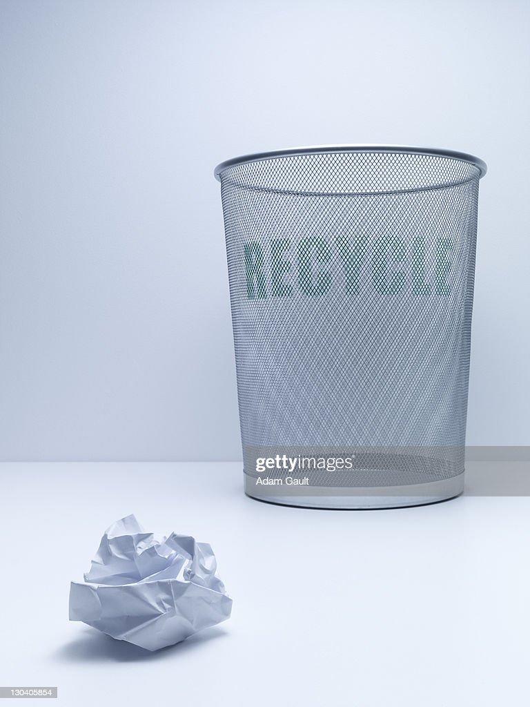 Crumpled ball of paper beside recycling bin