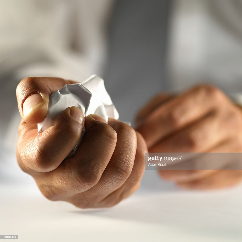 Crumpled ball of paper in man's hand