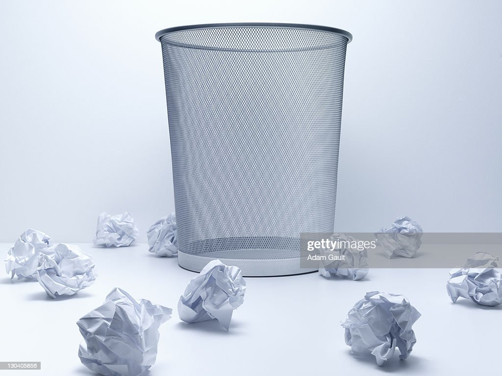 Crumpled balls of paper beside wastebasket