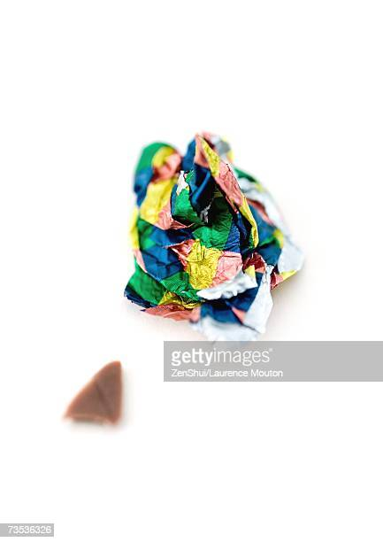 Crumpled candy wrapper and small piece of chocolate