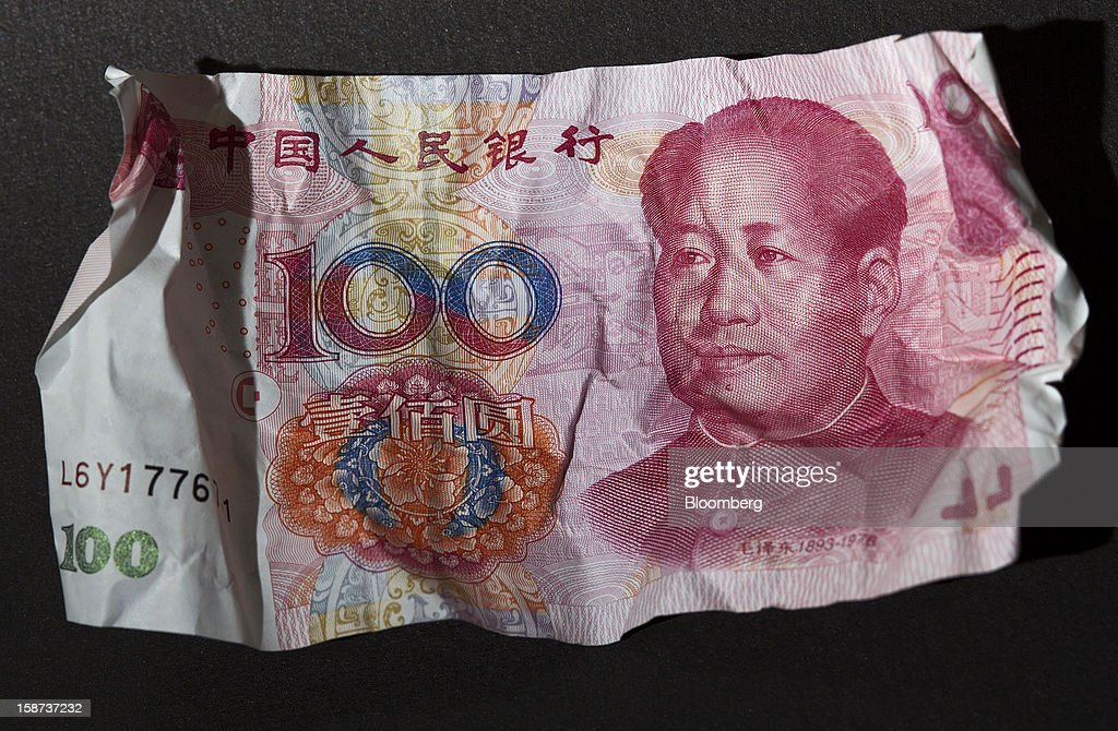 A crumpled Chinese one-hundred yuan banknote is arranged for a photograph in Hong Kong, China, on Wednesday, Dec. 26, 2012. China's yuan fell for a fourth day after the central bank set the currency's reference rate at a five-week low amid concern budget deficits in advanced nations will hurt the global economy. Photographer: Jerome Favre/Bloomberg via Getty Images