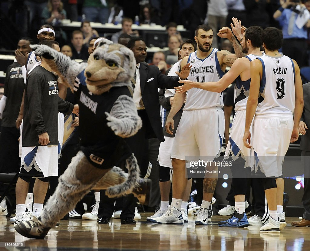 Crunch, mascot for the Minnesota Timberwolves, performs as Nikola Pekovic #14 of the Minnesota Timberwolves congratulates teammate Kevin Love #42 and Ricky Rubio #9 on tying the game in the final seconds of the fourth quarter in the season opening game against the Orlando Magic on October 30, 2013 at Target Center in Minneapolis, Minnesota. The Timberwolves defeated the Magic 120-115 in overtime.