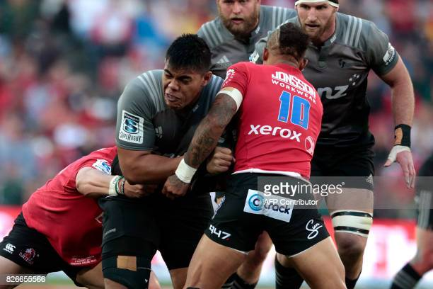 Crusaders' Australian Michael Alaalatoa runs with the ball as he is tackled by Lions' players during the Super XV rugby final match between Lions and...