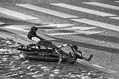 Crushed bike on the ground. Road accident  theme. Black and white photo